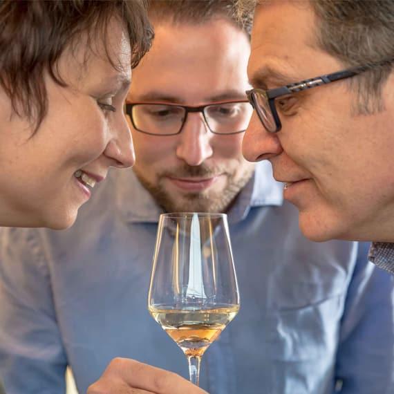 Petra, Johannes und Leopold Hofbauer-Schmidt blicken gemeinsam in ein Weinglas
