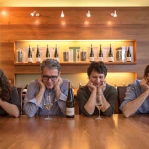 Familie Hofbauer-Schmidt sitzt mit Weingläsern bei Tisch
